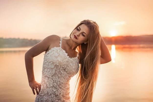 Kobieta ubrana w suknię wieczorową brzoskwiniowy kolor przeciw jeziorze