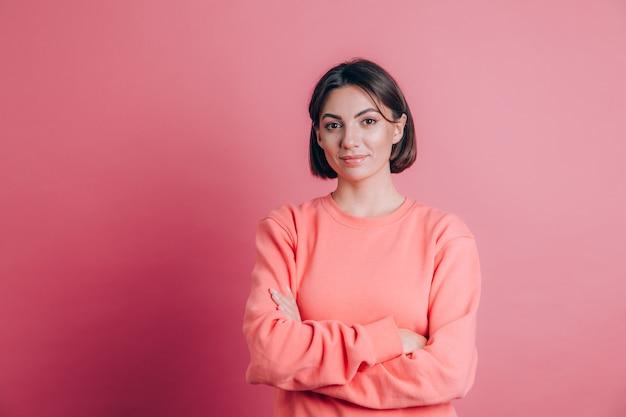 Kobieta ubrana w sweter na co dzień na tle szczęśliwa buźka uśmiecha się ze skrzyżowanymi rękami patrząc w kamerę. pozytywna osoba.