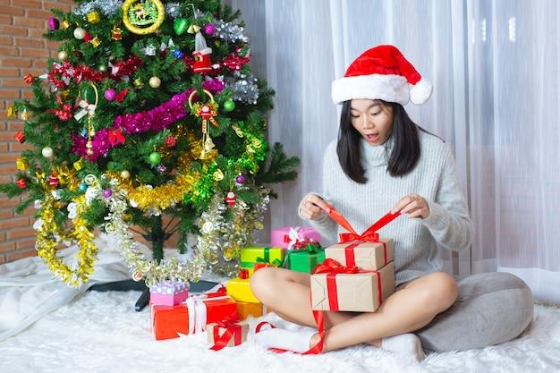 Kobieta ubrana w świąteczny kapelusz szczęśliwy z prezentem