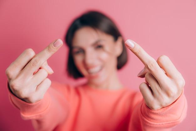 Kobieta ubrana w swobodny sweter na tle pokazując środkowy palec robi zły wyraz twarzy, prowokację i niegrzeczną postawę