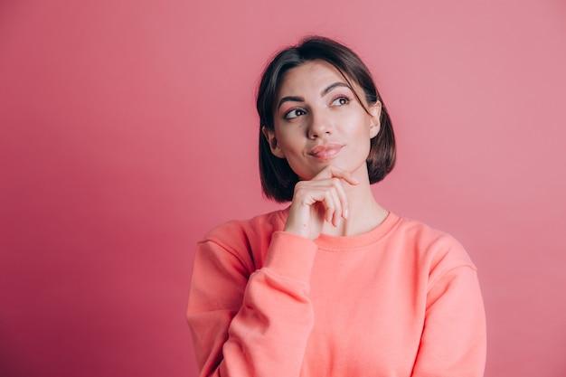 Kobieta ubrana w swobodny sweter na tle ręka na brodzie myśli o pytaniu, zamyślony wyraz. uśmiechnięty z zamyśloną miną