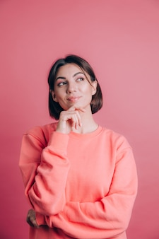 Kobieta Ubrana W Swobodny Sweter Na Tle Ręka Na Brodzie Myśli O Pytaniu, Zamyślony Wyraz. Uśmiechnięty Z Zamyśloną Miną Darmowe Zdjęcia