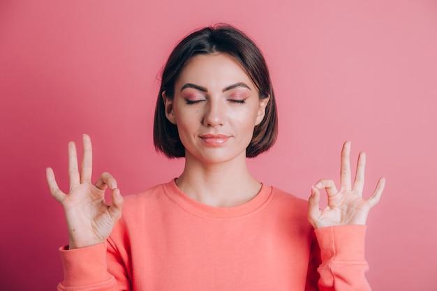 Kobieta ubrana w swobodny sweter na tle relaksuje i uśmiecha się z zamkniętymi oczami, robi gest medytacji palcami. koncepcja jogi.
