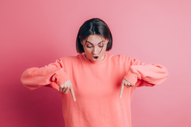 Kobieta ubrana w swobodny sweter na tle skierowaną w dół z palcami pokazującymi reklamę, zaskoczoną twarz i otwarte usta