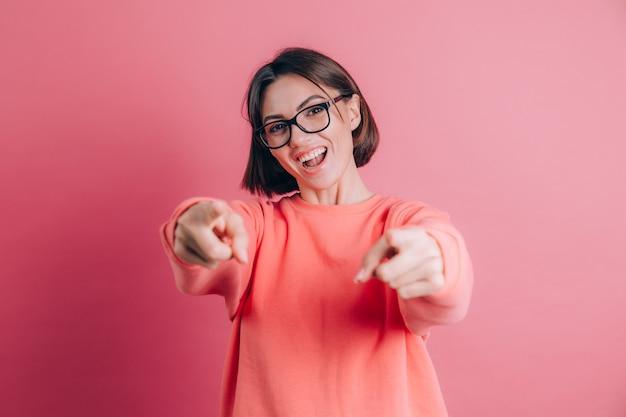 Kobieta ubrana w swobodny sweter na tle, wskazując na ciebie i aparat z palcami, uśmiechnięta pozytywnie i wesoło