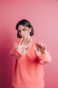 Kobieta ubrana w swobodny sweter na tle zniesmaczona wyrazem twarzy, niezadowolona i przerażona, robiąca obrzydliwą twarz z powodu reakcji niechęci