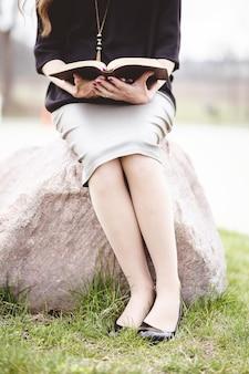 Kobieta ubrana w szarą spódnicę i czytająca książkę siedząc na skale