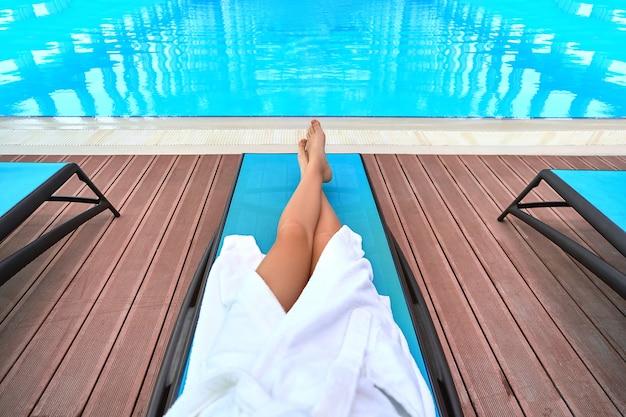 Kobieta ubrana w szlafrok z pięknymi, smukłymi, gładkimi długimi nogami leżąca na leżaku przy basenie podczas relaksu w ośrodku odnowy biologicznej. spokojny tryb życia i satysfakcja