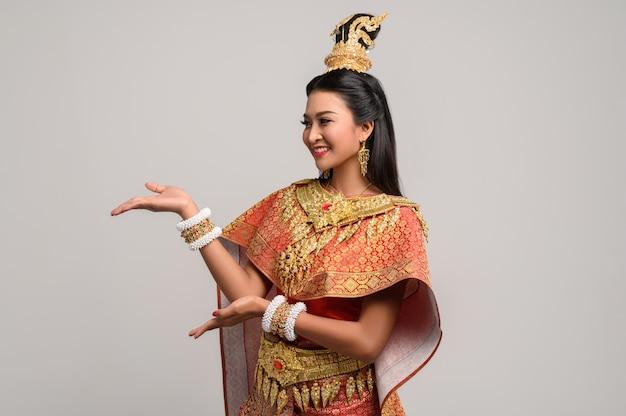 Kobieta ubrana w tajski strój, który zrobił symbol dłoni