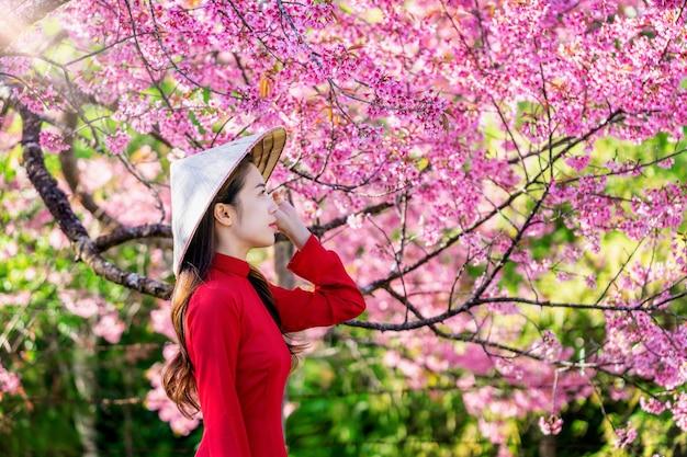 Kobieta ubrana w tradycyjną kulturę wietnamu w parku kwiat wiśni.