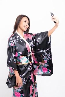 Kobieta ubrana w tradycyjne japońskie kimono na białym tle