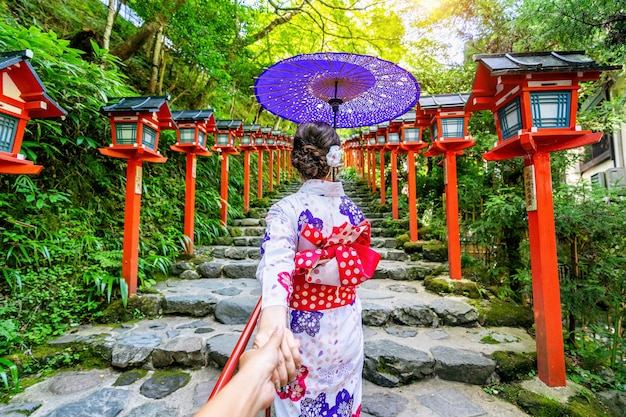 Kobieta ubrana w tradycyjne japońskie kimono trzyma mężczyznę za rękę i prowadzi go do świątyni kifune w kioto w japonii.