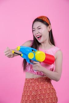 Kobieta ubrana w tradycyjne stroje ludowe thai trzyma pistolet na wodę na różowym tle.