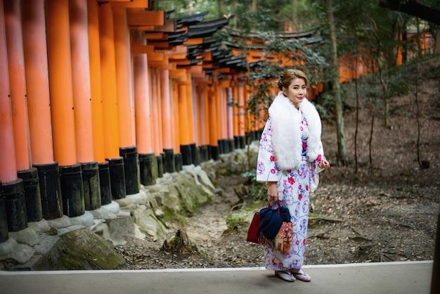 Kobieta ubrana w tradycyjny japoński strój spacerująca pod bramami tori w świątyni fushimi-inari, kioto, japonia