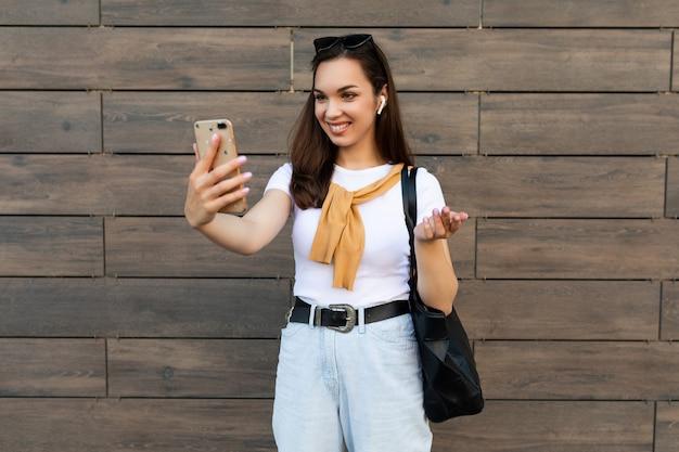 Kobieta ubrana w ubranie stojący na ulicy o komunikacji za pośrednictwem telefonu komórkowego, patrząc na smartfona