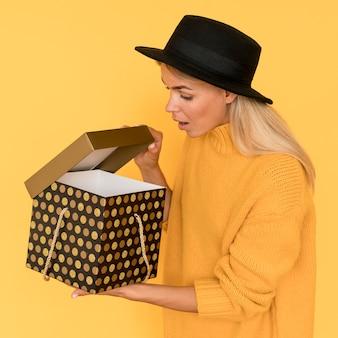 Kobieta ubrana w żółtą koszulę patrząc w pudełko