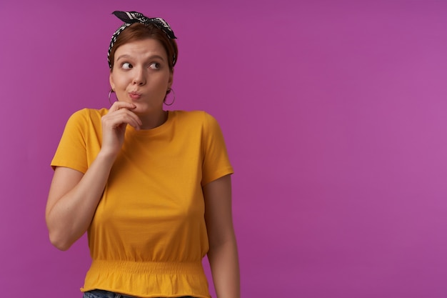 Kobieta ubrana w żółtą koszulkę i czarną chustkę emocja zestresowana zdezorientowana zdumiona zdumiona zdziwiona uważne spojrzenie na bok dotyk twarz nieśmiała pozowanie na fioletowej ścianie