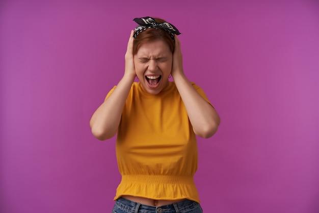 Kobieta ubrana w żółtą modną bluzkę i czarną chustkę z rękami w uszach emocja zestresowany krzyk z zamkniętymi oczami ból głowy pozowanie na fioletowej ścianie