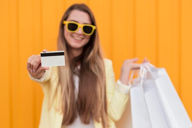 Kobieta ubrana w żółte ubrania, trzymając kartę zakupów