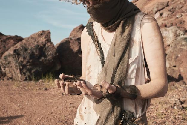 Kobieta uchodźczyni w podartych ubraniach patrząca na swoje brudne ramiona stojąc na pustyni