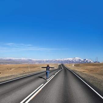 Kobieta ucieka na pustej drodze na wiejskiej stronie widok wzdłuż drogi chuysky republika ałtaju rosja