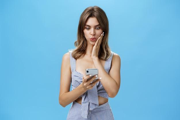 Kobieta ucząca się szokującej plotki, otrzymująca wiadomość w sieci społecznościowej od przyjaciela czytającego wiadomości ze smartfona, składane usta wpatrujące się podekscytowany w ekran smartfona przyciskający dłoń do policzka ze zdumienia