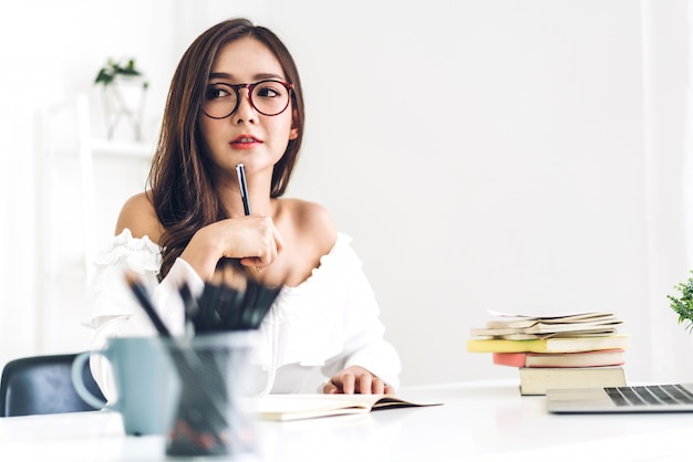 Kobieta uczeń siedzi, studiuje i uczy się online z laptopem i czyta książkę przed egzaminem w domu. edukaci pojęcie
