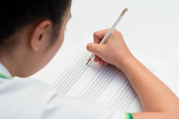 Kobieta uczeń wypełnia out odpowiada test z ołówkiem