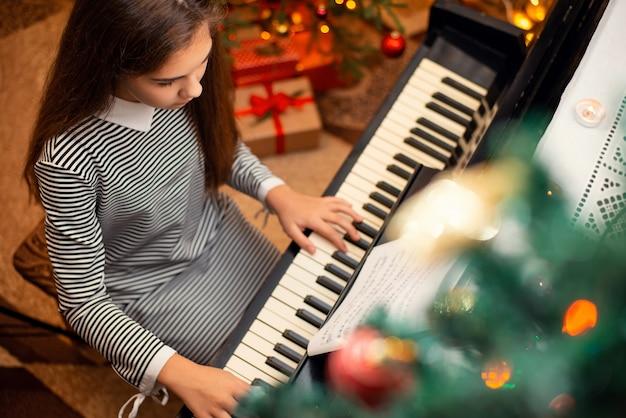 Kobieta uczennica w czarno-białe paski sukienka gra na pianinie z prezentami świątecznymi w tle