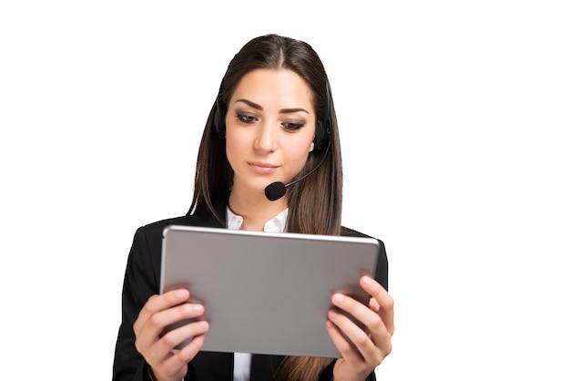 Kobieta uczestnicząca w zdalnym spotkaniu przy użyciu tabletu i zestawu słuchawkowego
