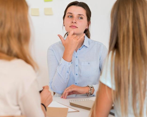 Kobieta uczy języka migowego innych ludzi