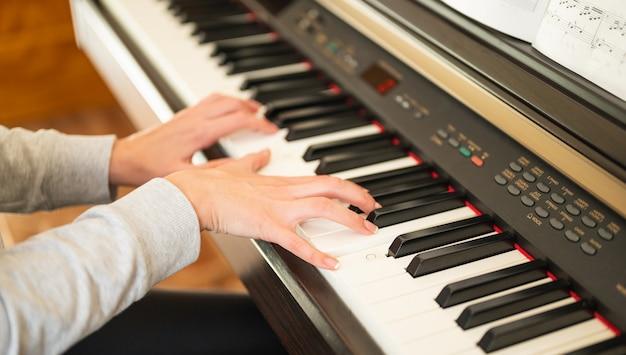 Kobieta uczy się gry na pianinie elektronicznym