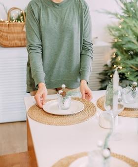 Kobieta udekoruje rustykalny świąteczny stół w domu rodzinne wakacje