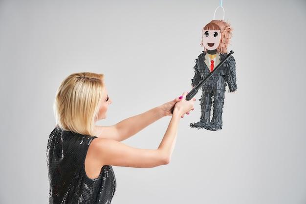 Kobieta uderzająca męską piniatę na szarym tle