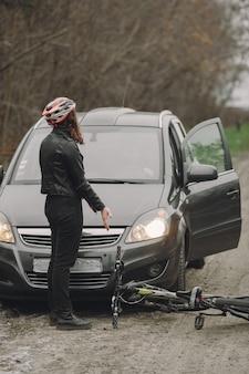 Kobieta uderzyła w samochód. dziewczyna w kasku. ludzie kłócą się o wypadek.
