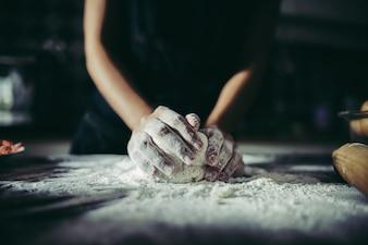 Kobieta ugniata ciasto dla robi pizzy na drewnianym. Gotowanie koncepcja.