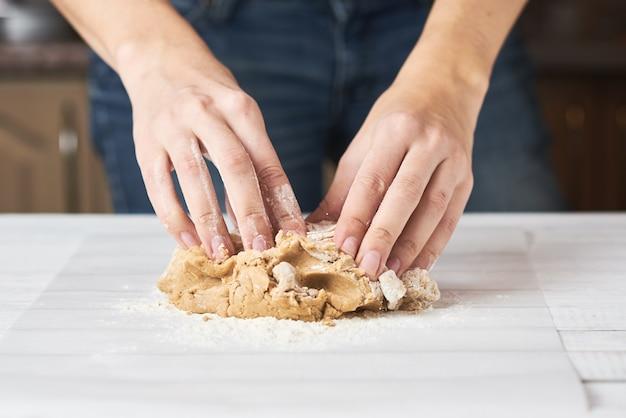 Kobieta ugniata ciasto z rękami w kuchni