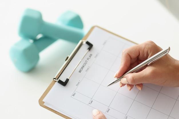 Kobieta układa plan treningowy na tydzień przy hantlach