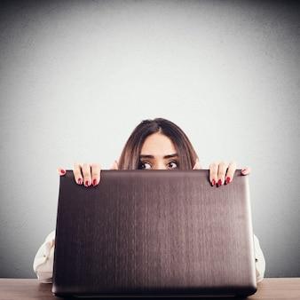 Kobieta ukryta za ekranem komputera skrycie zerka