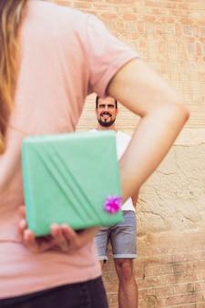 Kobieta ukrywanie prezent za plecami dając niespodziankę jej chłopaka