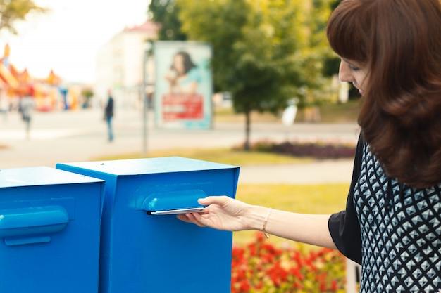 Kobieta umieszcza litery w skrzynce pocztowej