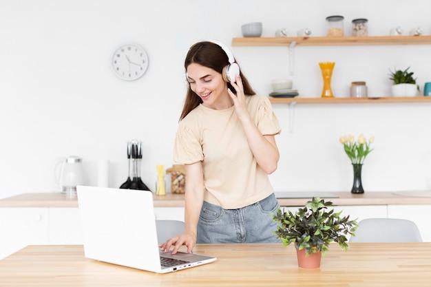 Kobieta umieszcza muzykę na słuchawkach z laptopa