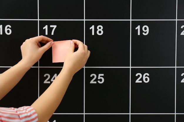 Kobieta umieszcza naklejkę na kalendarzu pokładowym, zbliżenie