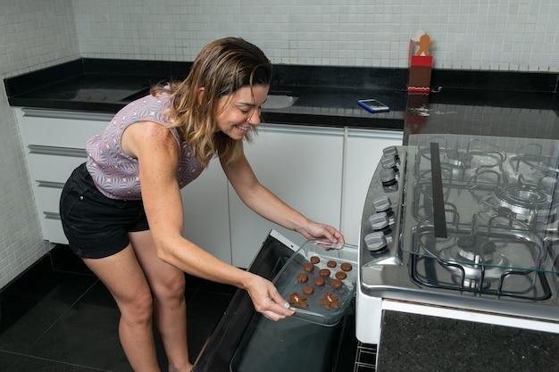 Kobieta umieszczenie naczynia do pieczenia szkła z ciasteczkami do pieczenia w piekarniku.