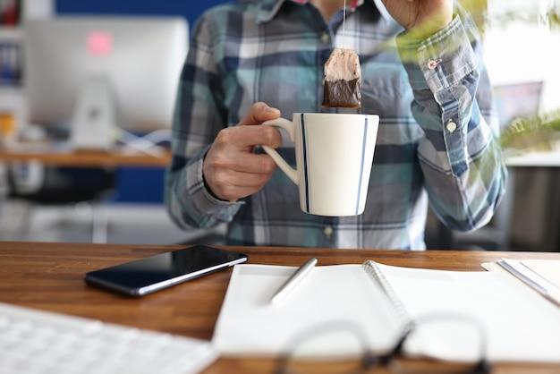 Kobieta umieszczenie torebkę herbaty w filiżance w tabeli zbliżenie