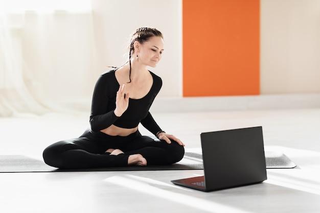 Kobieta, uniwersalna trenerka jogi, wita uczniów przy laptopie przed treningiem online