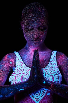 Kobieta uprawia jogę, ruchy rąk, rozgrzewkę ciała. kosmos art girl w świetle ultrafioletowym. całe ciało pokryte jest kolorowymi kroplami. joga astralna. hałas, nieostry