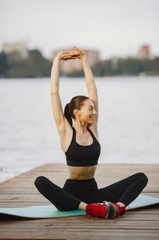Kobieta uprawiająca zaawansowaną jogę nad wodą