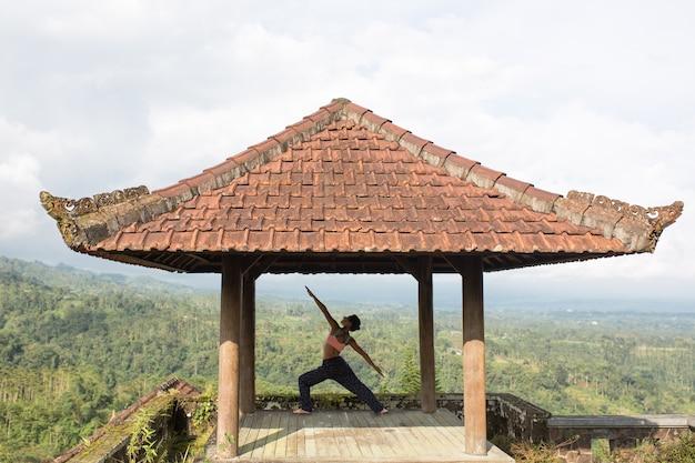 Kobieta uprawiania jogi w tradycyjnej altanie balinesse