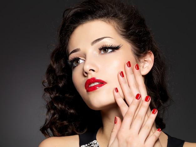 Kobieta uroda moda z czerwonymi paznokciami, ustami i złotym makijażem oczu